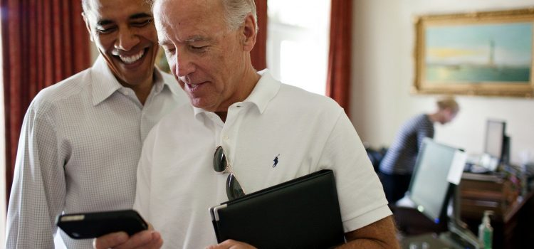 Photo of Joe Biden and Barack Obama looking at the screen of a phone being held by Biden