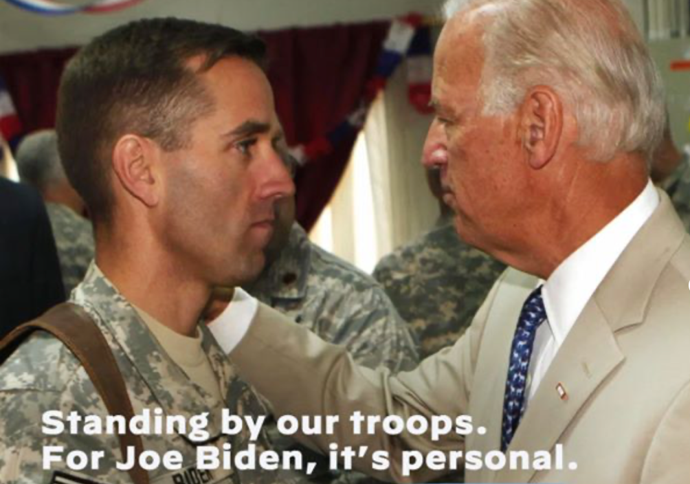 """Body from Biden ad. The ad shows Biden affectionately placing his hand on his son Beau Biden. Beau Biden is dressed in military fatigues. The bottom of the image includes the following statement: """"Standing by our troops. For Joe Biden, it's personal."""""""