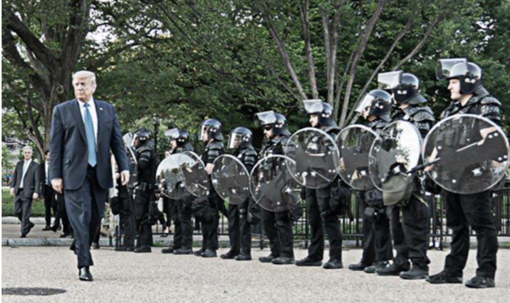 Body of ad by Biden. The ad shows Trump walking by a line of armed security forces.