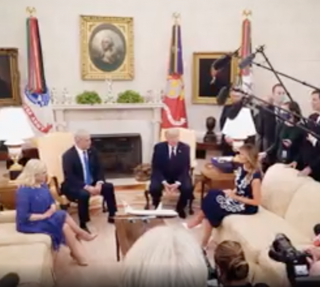 Paused video from a Trump ad. The scene shows President Trump and three other individuals sitting in the oval office with members of the press holding cameras and microphones to document the event.