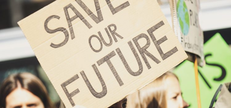 """Young adult holding a """"SAVE OUR FUTURE"""" sign. Other people appear behind the young adult, one of whom is also holding a sign with a picture of the globe."""