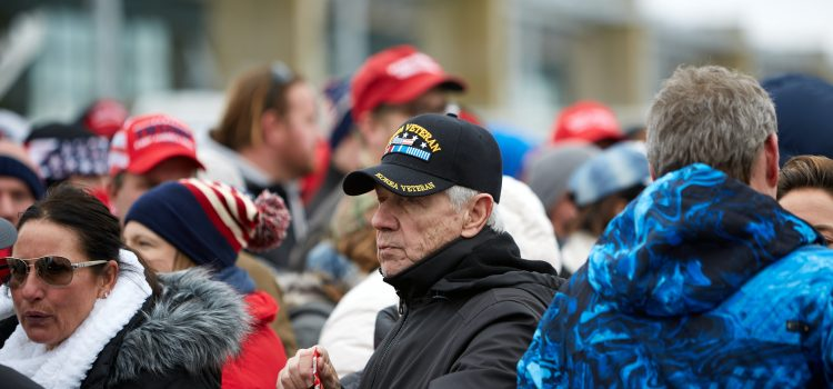 """Crowd of people dressed in winter clothes with US-themed colors. A person with a """"Korea Veteran"""" hat appears in the center of the photo."""