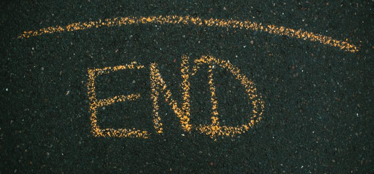 """A line with """"END"""" written below it on the pavement."""