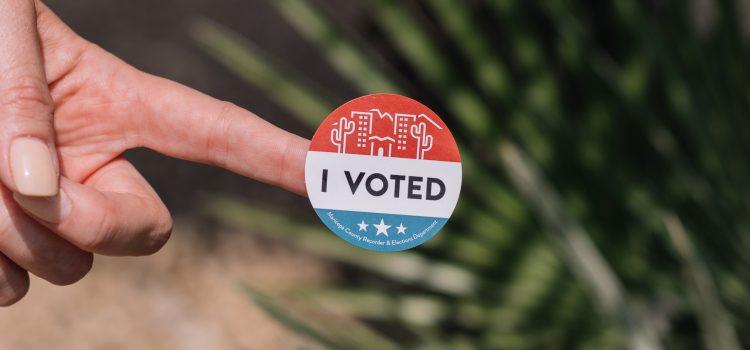 "Finger holding a ""I VOTED"" sticker"